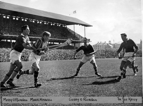 Mark Marnell brings out the ball through a cluster of Cork forwards in the 1947 Final.