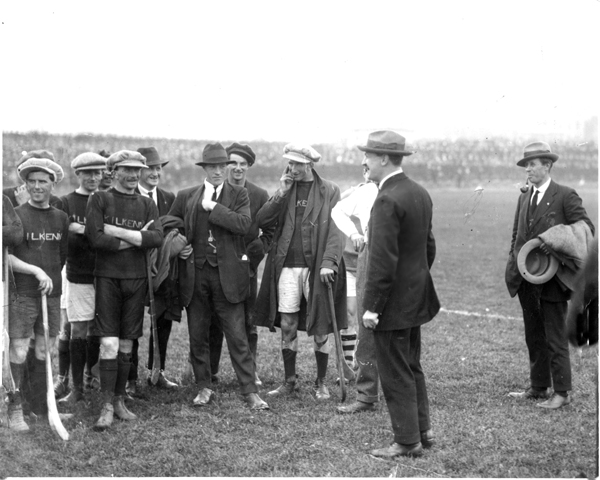 """Michael Collins addresses the Kilkenny team before the Leinster Final against Dublin, Sept 1921.<br /> In one of his first appearances after the Truce, Collins said - """"You are not only upholding the great game, but you are also upholding one of the most ancient and cherished traditions in Ireland.""""<br /> From left:- Paddy Donoghue (Dicksboro), Mattie Power (Dicksboro), Dick Grace (Tullaroan), Michael Joyce (Callan), Martin Egan (Threecastles), Bill Kenny (Lisdowney), Jack Holohan (from Johnstown played with Tullaroan), Michael  Collins and Harry Boland. Collins and Boland, (Chairman, Dublin Co Board and Sinn Fein TD for Roscommon) though great friends, found themselves on opposite sides in the Civil War which would claim both their lives within a year."""