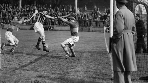 Liam Reidy scores a point in the 1950 League Final against Mick Byrne and Tony Reddan of Tipp.