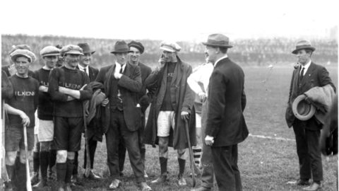 """Michael Collins addresses the Kilkenny team before the Leinster Final against Dublin, Sept 1921. In one of his first appearances after the Truce, Collins said - """"You are not only upholding the great game, but you are also upholding one of the most ancient and cherished traditions in Ireland."""" From left:- Paddy Donoghue (Dicksboro), Mattie Power (Dicksboro), Dick Grace (Tullaroan), Michael Joyce (Callan), Martin Egan (Threecastles), Bill Kenny (Lisdowney), Jack Holohan (from Johnstown played with Tullaroan), Michael Collins and Harry Boland. Collins and Boland, (Chairman, Dublin Co Board and Sinn Fein TD for Roscommon) though great friends, found themselves on opposite sides in the Civil War which would claim both their lives within a year."""